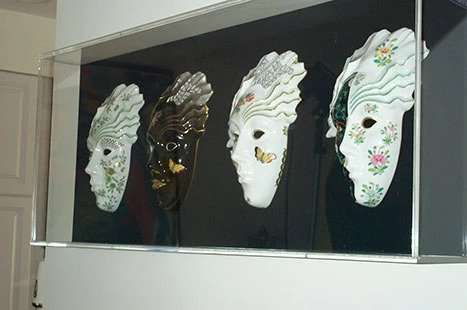 4 masks in plastic frame on wall